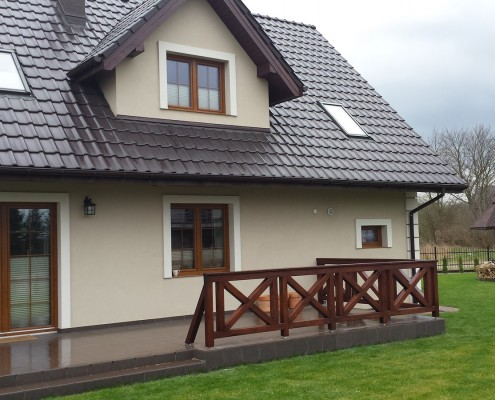 Dom jednorodzinny z tarasem ozdobionym tradycyjnymi balustradami drewnianymi