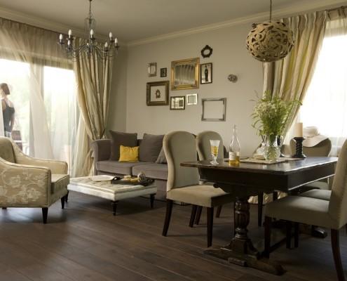 Przytulny salon w spokojnej kolorystyce. Zabytkowy stół z ciemnego drewna odzyskał w nim dawną świetność.