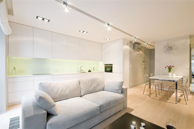 Biały salon połączony z kuchnią i jadalnią HomeSquare