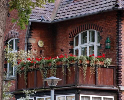 Ten mieszczański balkon ozdobiony kwiatami wpasowałby się tak samo dobrze w polskie, jak i angielskie podwórze.