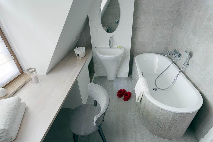 Aranżacja szarej łazienki z toaletką na poddaszu