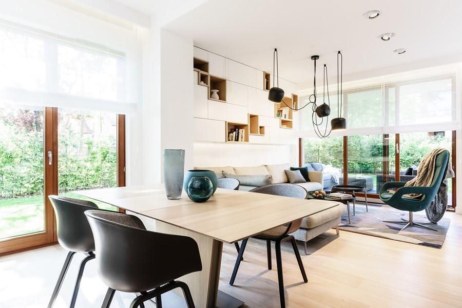 Salon otwarty na kuchnię i jadalnię w nowoczesnym apartamencie