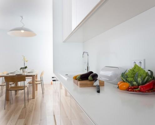 Minimalistyczna jadalnia z aneksem kuchennym w bieli