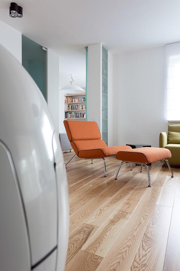 Pomarańczowy fotel z podnóżkiem w nowczesnym stylu