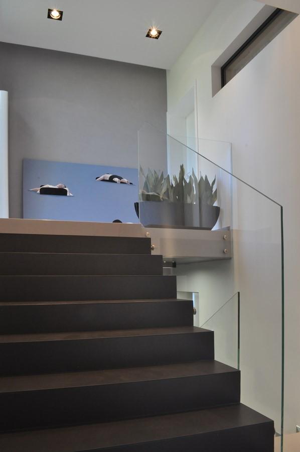 Schody ze szklaną balustradą w minimalistycznym stylu