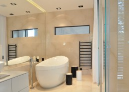Szkło i kamień w przestronnej łazience w nowoczesnym stylu