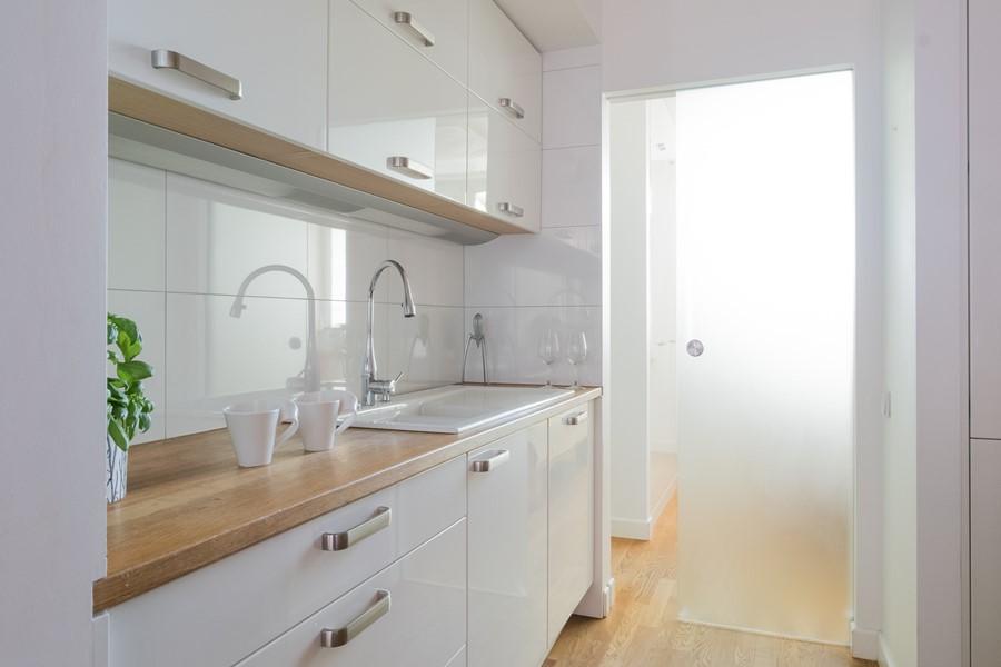 Nowoczesna biała kuchnia z drewnianymi blatami