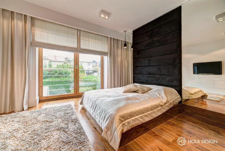 Piękna sypialnia z tapicerowaną ścianą szykowny minimalizm