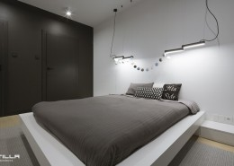 Minimalistyczna sypialnia z nowoczesnym oświetleniem Tilla Architects
