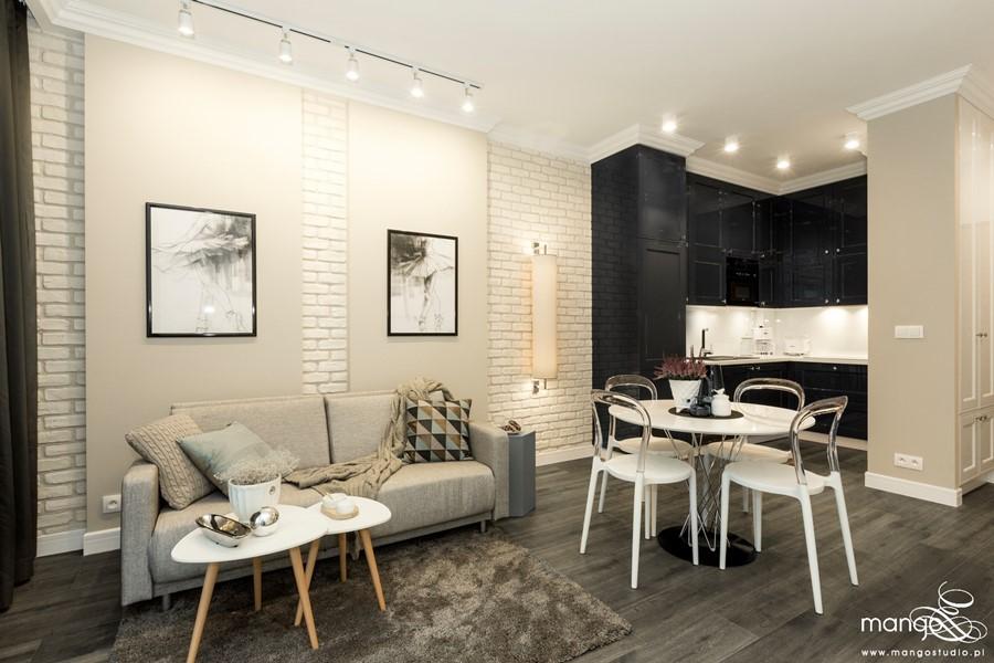 Aranżacja eklektycznego salonu z aneksem kuchennym Mango Studio - Ściana z cegły