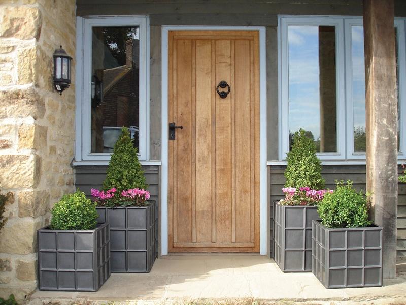 Klasyczne wejście do domu z donicami ogrodowymi