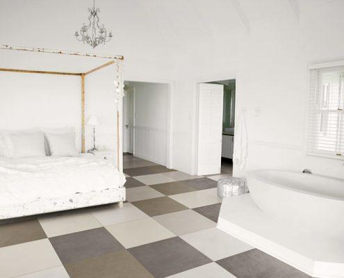 Biała sypialnia z wanną i kontrastującą podłogą