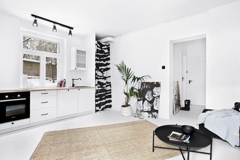 Minimalistyczny salon i aneks kuchenny z klasycznymi akcentami