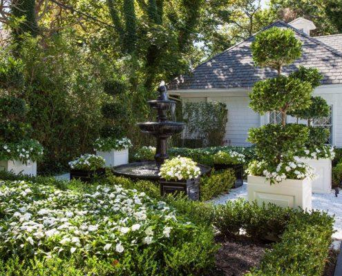 Zielony ogród z klasycznymi donicami i fontanną