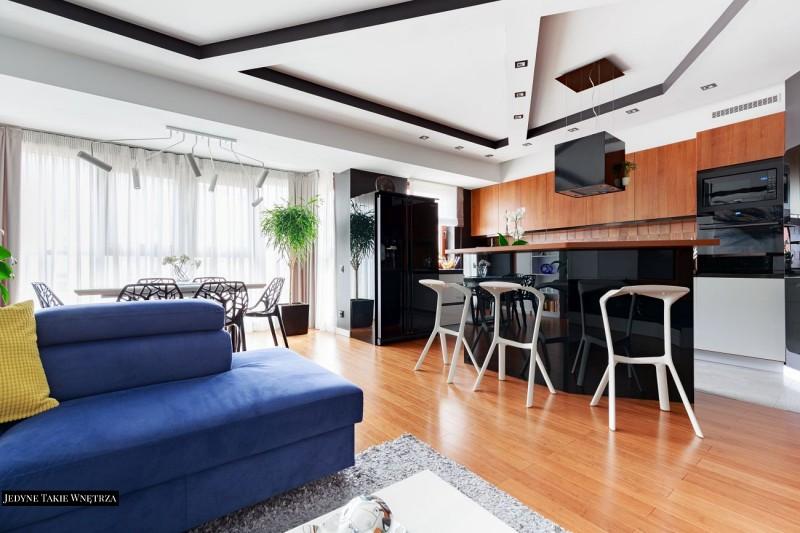 Nowoczesny apartamemt w bieli i czerni przełamanych drewnem