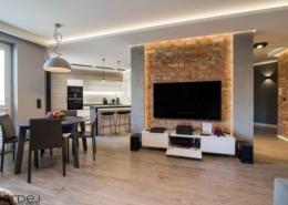 Minimalistyczny salon i jadalnia z ceglaną ścianą