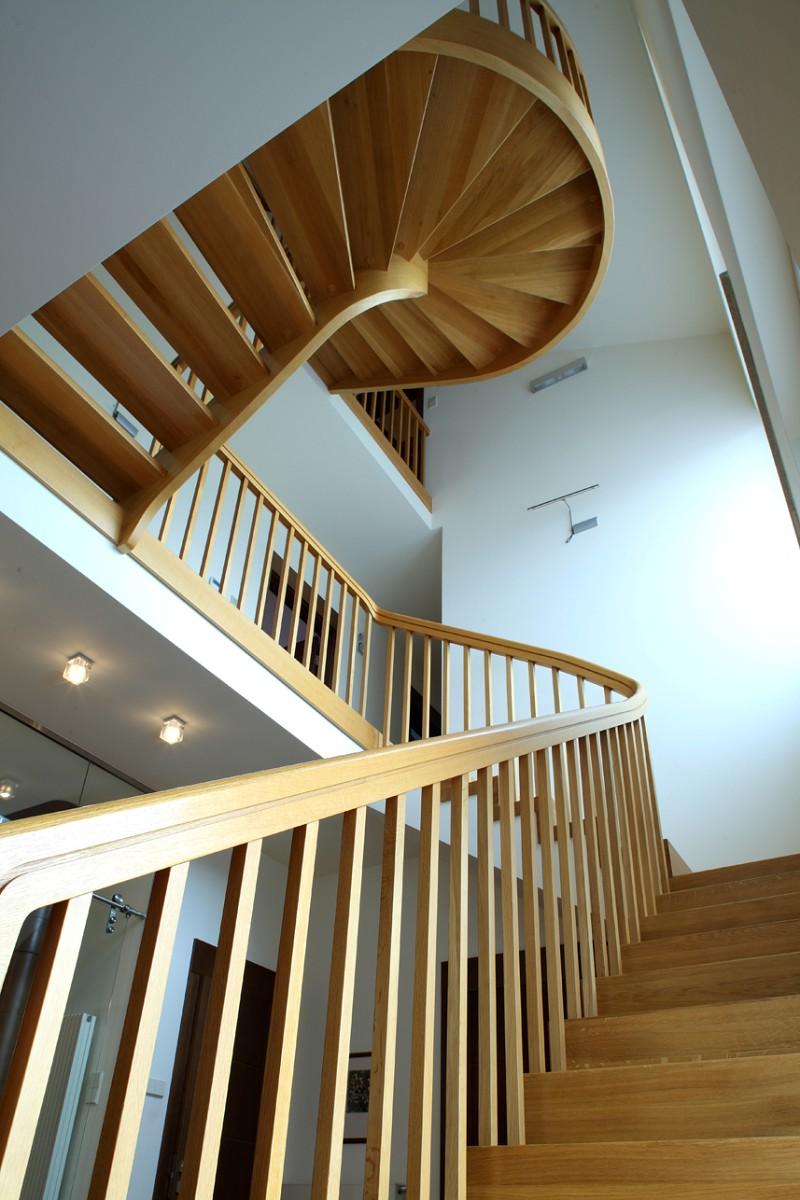 Drewniane, półspiralne schody w przedpokoju